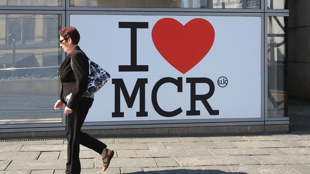 A woman walks past a 'I Love Manchester' sign ahead of the Manchester Arena National Service of Commemoration at Manchester Cathedral to mark one year since the attack on Manchester Arena, Tuesday May 22, 2018. (Peter Byrne/PA via AP)