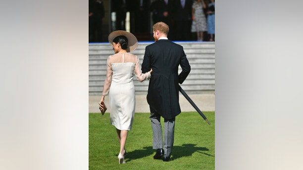 Meghan, the Duchess of Sussex and her husband Prince Harry walk as they attend a garden party at Buckingham Palace in London, Tuesday May 22, 2018, their first royal engagement since marrying on Saturday. The event is part of the celebrations to mark the 70th birthday of Prince Charles.  (Dominic Lipinski/Pool Photo via AP)