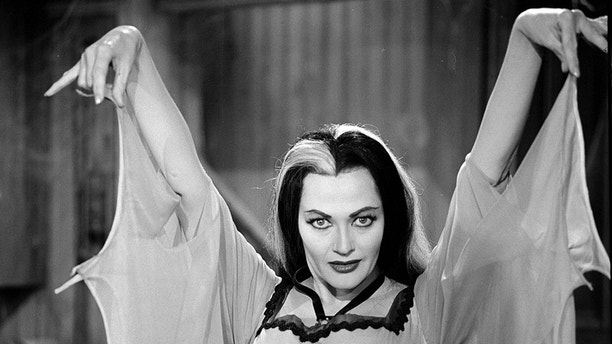 Canadian actress Yvonne de Carlo raises her arms and gestures as she wears a bat-winged dress in her role as 'Lily Munster' in a still from the CBS television situation comedy 'The Munsters' episode 'My Fair Munster,' May 1, 1964. (Photo by CBS Photo Archive via Getty Images)