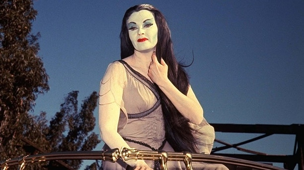 """Actress Yvonne De Carlo, dressed for her role as Lily Munster in the film """"Munster, Go Home,"""" poses in her car in the parking lot outside Universal Studios March 25, 1966.  (AP Photo)"""