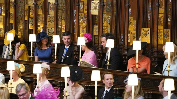 From left, George Clooney, Amal Clooney, Silver Tree, Abraham Levy, Celine Khavarani, Markus Anderson, Janina Gavankar, and Jill Smoller are seated prior to the start of the wedding ceremony of Prince Harry and Meghan Markle at St. George's Chapel in Windsor Castle in Windsor, near London, England, Saturday, May 19, 2018. (Dominic Lipinski/pool photo via AP)