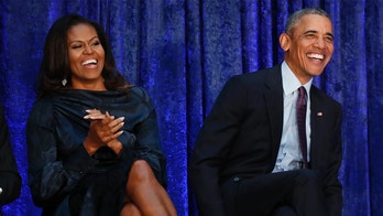 Former U.S. President Barack Obama sits with former first lady Michelle Obama prior during the unveiling of their portraits at the Smithsonian's National Portrait Gallery in Washington, U.S., February 12, 2018. REUTERS/Jim Bourg - HP1EE2C1B3X0Y