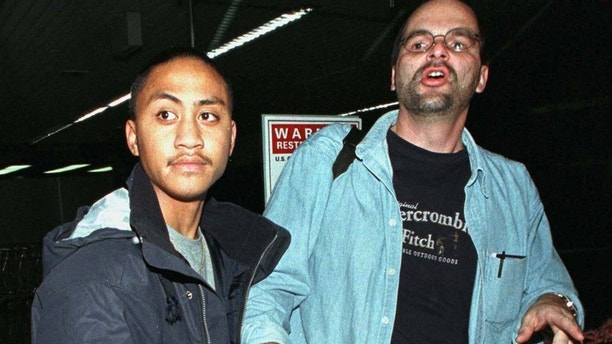 Fifteen-year-old Vili Fualaau (L), clutching a French present for his children by convicted statutory rapist, teacher and 36-year-old Mary Kay Letourneau, returns to SeaTac Airport with his lawyer Bob Huff October 25 after promoting his new book in Paris. Fualaau first fathered a child with Letourneau when he was a 13-year-old sixth-grade student of Letourneau's at the Highline School District near Seattle. Letourneau is now serving a seven year sentence for two counts of second-degree child rape for her relationship with Fualaau. Letourneau, who gave birth last week to her second child from her relationship with Fualaau, is serving her term at the state prison for women in Gig Harbor, Washington.APB/KM/JDP - RP1DRIGSJAAB