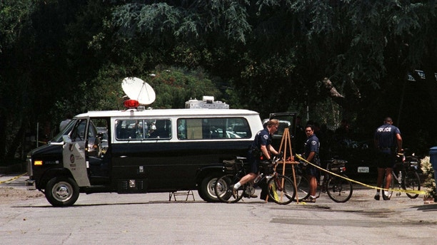 A Los Angeles Police Department van sits in the street near the driveway to the home of actor Phil Hartman May 28, 1998 in Encino,California.