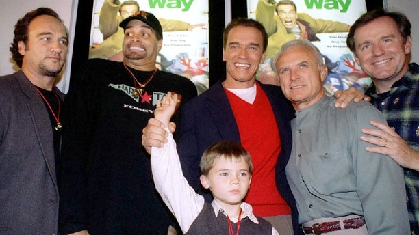 "Actor Arnold Schwarzenegger, red sweater, is flanked by co-stars, from left, James Belushi, Sinbad, Robert Conrad and Phil Hartman and holds the hand of Jake Lloyd, before attending the premiere oftheir new film, ""Jingle All The Way, at the Mall of America in Bloomington, MN, November 16, 1996."
