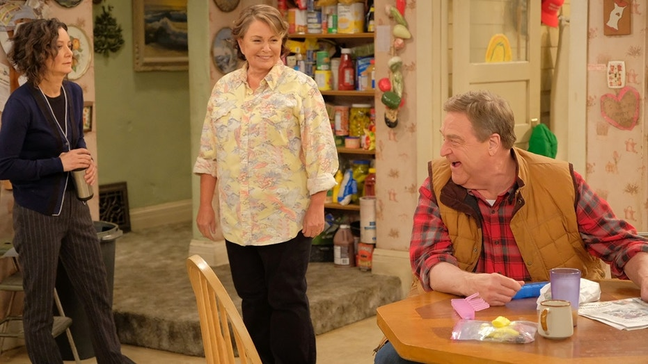 """Sara Gilbert, left, struggled to fight back tears as she addressed the cancellation of """"Roseanne"""" where she starred beside Roseanne Barr, center, and John Goodman, right."""