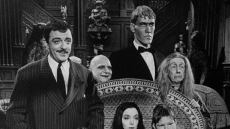 "Carolyn Jones (C, sitting) and John Astin (L), with other cast members, during scene from program ""The Addams Family."""