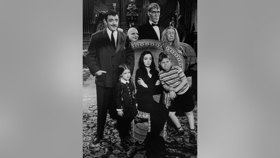 """Carolyn Jones (C, sitting) and John Astin (L), with other cast members, during scene from program """"The Addams Family."""""""