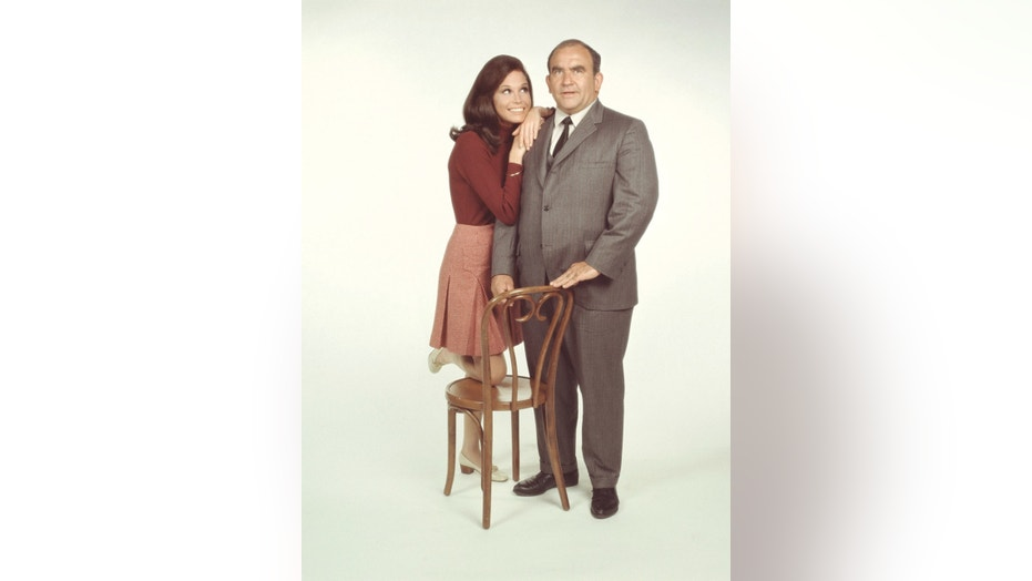 "American actors Mary Tyler Moore, as Mary Richards, and Ed Asner, as Lou Grant, pose for a publicity photo for the CBS comedy, ""The Mary Tyler Moore Show,"" in 1971."