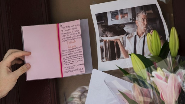 A mourner reads a sympathy card left for Anthony Bourdain at a make shift memorial outside the building that once housed Le Halles restaurant on Park Avenue, Friday, June 8, 2018, in New York. Bourdain, the celebrity chef and citizen of the world who inspired millions to share his delight in food and the bonds it created, was found dead Friday in his hotel room in France while working on his CNN series on culinary traditions. He was 61. (AP Photo/Mary Altaffer)