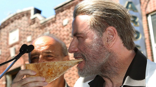 """This image released by Starpix shows actor John Travolta, star of the upcoming film """"Gotti,"""" eating a slice of pizza from Lenny's Pizzeria in the Brooklyn borough of New York on Tuesday, June 12, 2018. The pizzeria was highlighted in the 1977 blockbuster """"Saturday Night Fever"""" when Travolta's Tony Manero character ordered two slices and ate them one on top of the other as he walked down the street. The restaurant has become a popular tourist spot with people still ordering the double-decker slices. (Patrick Lewis/Starpix via AP)"""