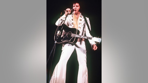 FILE - In this 1973 file photo, Elvis Presley sings during a concert. A private jet once owned by Elvis Presley that has sat on a runway in New Mexico for nearly four decades is back on the auction block. The online auction site IronPlanet announced this week that plane with red velvet seats had returned the market after its current owner bought it last year for $430,000. (AP Photo/File)