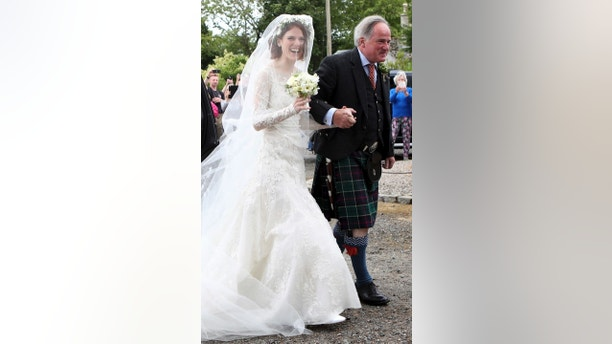 """Rose Leslie is escorted by her father Sebastian as they arrive for her wedding at Rayne Church, Kirkton of Rayne in Aberdeenshire, Scotland, Saturday June 23, 2018. Former """"Game of Thrones"""" co-stars Kiet Harington and Rose Leslie are set to marry near the bride's family castle in Scotland. Fans of the show gathered outside 900-year-old Wardhill Castle in northeast Scotland to catch a glimpse of the two British actors. (Jane Barlow/PA via AP)"""