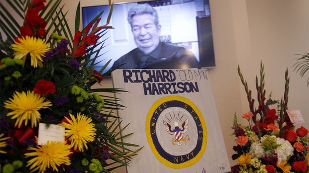 Richard Harrison is shown in the TV show Pawn Stars on the screen at his memorial service at Palm Mortuary in Las Vegas, Sunday, July 1, 2018. Well known as the patriarch in the Pawn Stars TV show, he died Monday after a long battle with Parkinson's disease. A public viewing was open in the morning followed by a service for family and friends. (Rachel Aston/Las Vegas Review-Journal via AP)