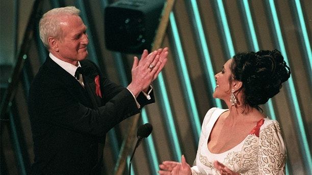 Paul Newman and Elizabeth Taylor applaud each other during the Academy Awards on March 30, 1992, in Los Angeles, California. The pair presented the Best Picture Oscar.    REUTERS/Gary Hershorn - GF2DUSHOUXAB