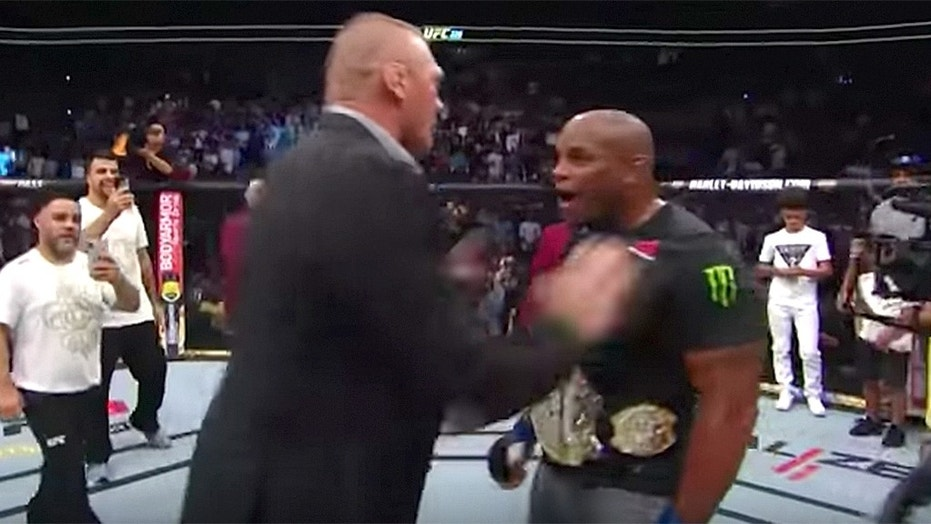 Brock Lesnar confronts Daniel Cormier in the octagon.