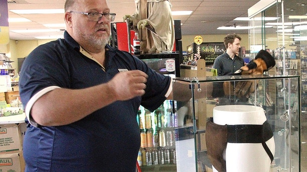 "FILE - In this May 2, 2018 file photo, Blockbuster Alaska General Manager Kevin Daymude moves a display case featuring the jockstrap worn by actor Russell Crowe in the 2005 movie ""Cinderella Man"" at a Blockbuster video store in Anchorage, Alaska. Despite the gift of the jockstrap from HBO's John Oliver to bring traffic into the store, Daymude said the last two Blockbuster Video locations in Alaska will rent their last video on Sunday, July 15, 2018, apparently leaving the last Blockbuster Video in Bend, Ore. (AP Photo/Mark Thiessen, File)"
