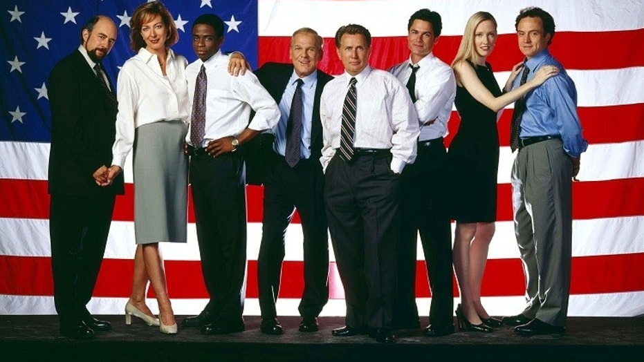 """West Wing"" cast members shown (L-R) are Richard Schiff, Allison Janney, Dule Hill, John Spencer, Martin Sheen, Rob Lowe, Janel Moloney and Brad Whitford."