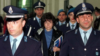 Patrizia Reggiani (C), ex-wife of slain fashion mogul Maurizio Gucci, is surrounded by police while leaving a Milan court as the jury retires to decide its verdict November 3. Reggiani, 50, was found guilty of plotting the murder of her ex-husband and sentenced to jail for 29 years. Four other accomplices were also found guilty with all receving jail sentences.