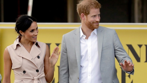 Britain's Prince Harry, right,  and his wife Meghan the Duchess of Sussex wave at onlookers as they arrive for their visit to the launch of the Nelson Mandela Centenary Exhibition, marking the 100th anniversary of anti-apartheid leader's birth, at the Queen Elizabeth Hall in London, Tuesday, July 17, 2018. (AP Photo/Matt Dunham)
