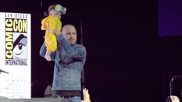 "Aaron Paul holds his daughter Story Annabelle in the air as she is dressed as his character Jesse Pinkman at the ""Breaking Bad"" 10th Anniversary panel on day one of Comic-Con International on Thursday, July 19, 2018, in San Diego.(Photo by Richard Shotwell/Invision/AP)"