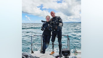 Ronda Rousey and Paul De Gelder pose before their dive beneath the waters off the Fiji coast.