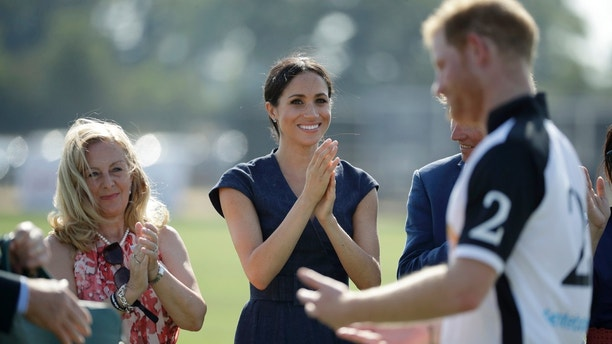 Meghan, Duchess of Sussex applauds Prince Harry, foreground, during the presentation ceremony for the Sentebale ISPS Handa Polo Cup at the Royal County of Berkshire Polo Club in Windsor, England, Thursday, July 26, 2018. (AP Photo/Matt Dunham)