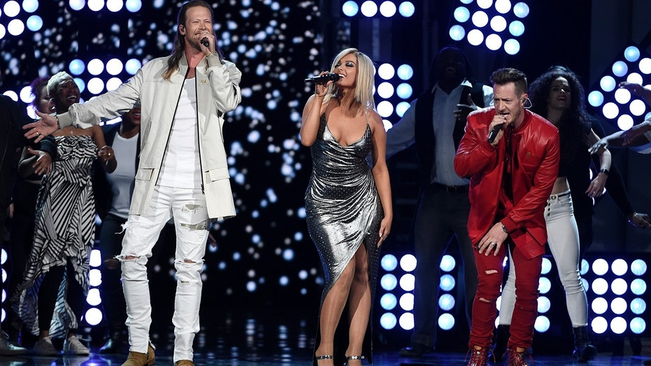 "In this April 15, 2018 file photo, Tyler Hubbard, right, and Brian Kelley, left, of Florida Georgia Line, and Bebe Rexha, center, perform ""Meant to Be"" at the 53rd annual Academy of Country Music Awards in Las Vegas. The crossover hit ""Meant To Be"" has broken a new record on the Billboard Hot Country chart, remaining in the No. 1 spot for 35 weeks."