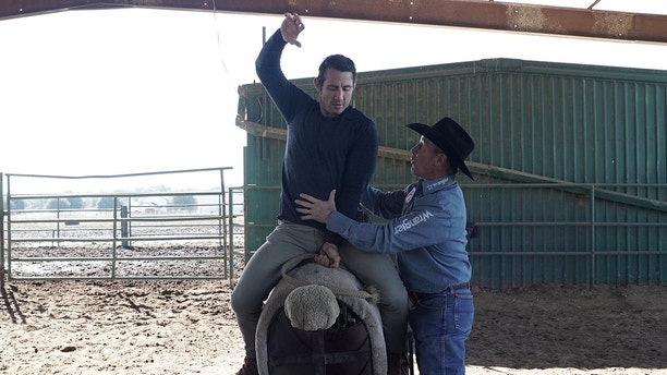 Champion Bullfighter Rob Smets helps Tim Kennedy learn how to ride a bull.