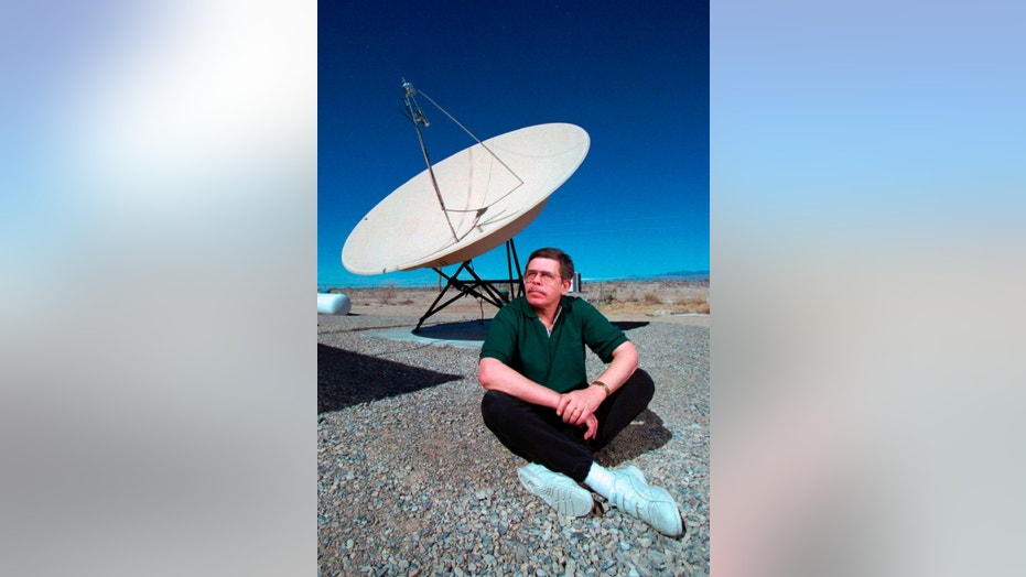 In this March 7, 1997, photo, shows late night talk show host Art Bell near a satellite dish at his Pahrump, Nev., home. Bell, was the original owner of Pahrump based radio station KNYE 95.1 FM.