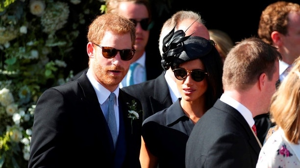 Britain's Prince Harry,  left and Meghan, the Duchess of Sussex join guests outside St Mary the Virgin Church after attending the wedding of Charlie van Straubenzee and Daisy Jenks, in Frensham, England, Saturday Aug. 4, 2018. Aug. 4 marks the 37th birthday of the Duchess. (Yui Mok/PA via AP)