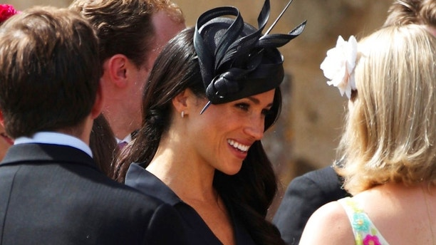 Meghan, the Duchess of Sussex, centre, talks to guests outside St Mary the Virgin Church after attending the wedding of Charlie van Straubenzee and Daisy Jenks with her husband Prince Harry, in Frensham, England, Saturday Aug. 4, 2018. Aug. 4 marks the 37th birthday of the Duchess. (Yui Mok/PA via AP)
