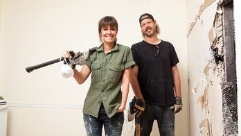 Hosts Leanne and Steve Ford in the midst of  demolishing a wall to open up space in the Faraci home, as seen on Restored By The Fords. (portrait)