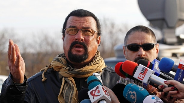 U.S. actor Steven Seagal talks to the media after he adopted Grivei, a stray dog from the Dogtown kennel in Uzunu, 40 km (24 miles) south of Bucharest November 17, 2013. Seagal said he wants to be an example to the people in Romania by adopting the dog, after Romania's top court ruled in favour of a law to kill tens of thousands of stray dogs from the streets of Bucharest in September after a four-year-old boy was mauled to death on September 2. The boy's death triggered street protests demanding action against the capital's more than 60,000 strays, who bite dozens of people every day and are also a deterrent for tourism. Parliament overwhelmingly backed the law that allows local administrations to put down dogs caught in public spaces if they are not adopted within two weeks. REUTERS/Bogdan Cristel (ROMANIA - Tags: ANIMALS ENTERTAINMENT) - RTX15HDZ