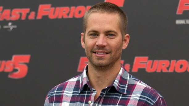 "FILE - In this April 29, 2011 file photo, actor Paul Walker poses during the photo call of the movie ""Fast and Furious 5,"" in Rome.  A coroner's report says the Porsche carrying Walker may have been going 100 mph or more before it crashed, killing both Walker and the driver. The report released Friday, Jan. 3, 2014, by the Los Angeles County coroner's office says that Roger Rodas, Walker's friend and financial adviser, was driving the 2005 Porsche Carrera GT at an unsafe speed, estimated by witnesses to be 100 mph or more. (AP Photo/Andrew Medichini, File)"