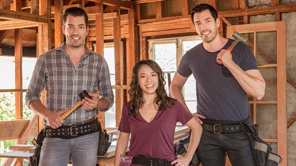Hosts Jonathan and Drew Scott pause with Drew's fiancee Linda in Drew's honeymoon house, which is undergoing an extensive remodel ahead of Drew and Linda's upcoming wedding, as seen on Property Brothers at Home: Drew's Honeymoon House.