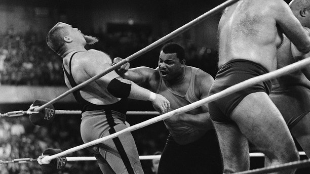"""Chicago Bears' William Perry, right, lands a punch on pro wrestler Jim """"The Anvil"""" Neidhart during the """"Over-The-Top-Rope"""" battle royal at Wrestlemania 2 on April 7, 1986 in Rosemont, Illiniois. Perry was eventually thrown from the ring in the event, which was won by Andre the Giant. (AP Photo/Charlie Bennett)"""