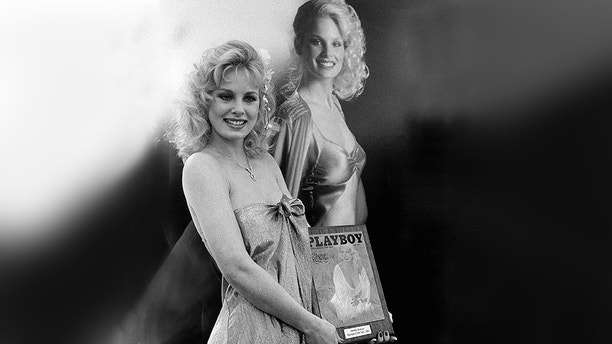 "Actress Dorothy Stratten, 20, of Vancouver, British Columbia poses in front of a huge poster of herself  Apr. 29, 1980 in Los Angeles as she was named the 1980 ""Playboy"" Playmate of the year. She will be featured on the cover of June ""Playboy"" and in an additional 17 pages of the issue. (AP Photo/Randy Rasmussen)"