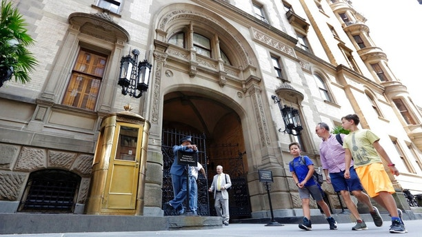 People walk by the entrance to the Dakota Apartments, in New York, Wednesday, Aug. 15, 2018, where John Lennon was shot by Mark Chapman in 1980. New York State Assemblywoman Nicole Malliotakis asked at a news conference for the State Parole Board to deny parole to Chapman when they meet next week. (AP Photo/Richard Drew)