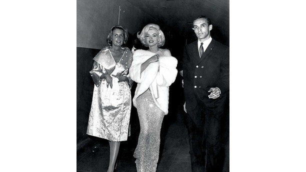Marilyn Monroe walks with friends on the evening that she sang Happy Birthday to President John F. Kennedy on his 45th birthday. She wears a form-fitting gown designed by Jean Louis, head designer for Columbia Pictures at the time. The see-through flesh-hued gown, sans undergarments, is embroidered with rhinestones. But she did accessorize with with earrings, a fur wrap and heels.