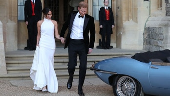 Britain's Prince Harry, Duke of Sussex, (R) and Meghan Markle, Duchess of Sussex, (L) leave Windsor Castle in Windsor on May 19, 2018 after their wedding to attend an evening reception at Frogmore House. (Photo by Steve Parsons / POOL / AFP)        (Photo credit should read STEVE PARSONS/AFP/Getty Images)