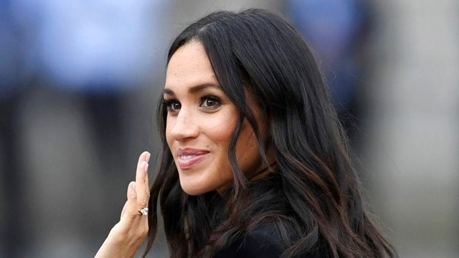 Meghan, Duchess of Sussex, waves as she visits Trinity college, in Dublin, Ireland, Wednesday, July 11, 2018.
