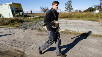 FILE - In this Dec. 1, 2008, file photo, Brad Pitt walks in the Lower 9th Ward between a home built by the Make It Right Foundation and a FEMA trailer in New Orleans. An attorney plans to sue Pitt's foundation over the degradation of homes built in an area of New Orleans that was among the hardest hit by Hurricane Katrina. (AP Photo/Alex Brandon, File)