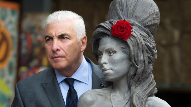 Mitch Winehouse poses for a picture with a statue of his late daughter, Amy Winehouse after it was unveiled in Camden's Stables Market, in London, England, Sunday, Sept. 14, 2014. Three years after her death the unveiling coincides with what would have been her 31st birthday. (AP Photo/Tim Ireland)