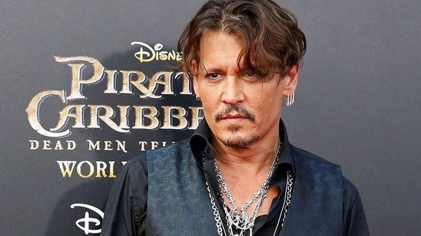 Actor Johnny Depp arrives on the red carpet for the global premiere of the film