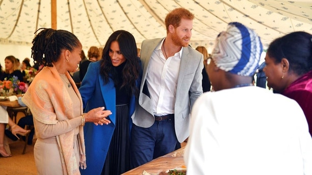 """Meghan, the Duchess of Sussex, centre, talks to her mother Doria Ragland, with Prince Harry at centre right, as they attend a reception for the cookbook """"Together"""", at Kensington Palace, in London, Thursday Sept. 20, 2018. The cookbook is being launched with an aim of raising money for victims of the Grenfell fire. (Ben Stansall/Pool Photo via AP)"""