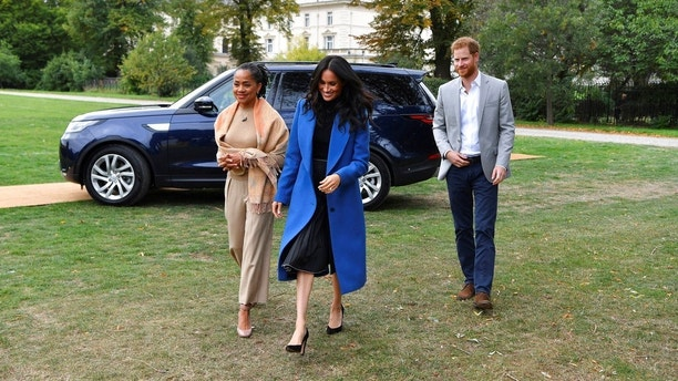 "Meghan, the Duchess of Sussex, centre, accompanied by Britain's Prince Harry, the Duke of Sussex and her mother Doria Ragland walk to attend a reception at Kensington Palace, in London, Thursday Sept. 20, 2018. Markle was joined by her mother for the launch of a cookbook aimed at raising money for victims of the Grenfell fire. Markle, now the Duchess of Sussex, hosted the reception beside her mother, Doria Ragland, to support the cookbook called ""Together."" (Ben Stansall/Pool Photo via AP)"