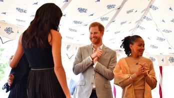 "Britain's Prince Harry and Doria Ragland, gesture as Meghan, the Duchess of Sussex, left, hugs a woman involved with the cookbook ""Together"" during a reception at Kensington Palace, in London, Thursday Sept. 20, 2018. The Duchess was joined by her mother Doria Ragland and husband Prince Harry for the launch of a cookbook aimed at raising money for victims of the Grenfell fire. (Ben Stansall/Pool Photo via AP)"