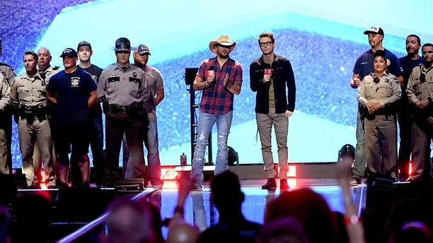 LAS VEGAS, NV - SEPTEMBER 21:  Jason Aldean (center L) and Bobby Bones (center R) speak onstage with first responders during the 2018 iHeartRadio Music Festival at T-Mobile Arena on September 21, 2018 in Las Vegas, Nevada.  (Photo by Kevin Winter/Getty Images for iHeartMedia)