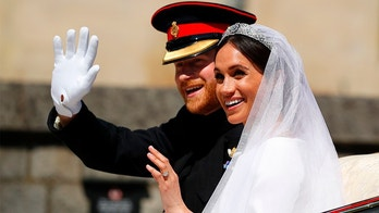 TOPSHOT - Britain's Prince Harry, Duke of Sussex and his wife Meghan, Duchess of Sussex wave from the Ascot Landau Carriage during their carriage procession on Castle Hill outside Windsor Castle in Windsor, on May 19, 2018 after their wedding ceremony. (Photo by PHIL NOBLE / POOL / AFP)        (Photo credit should read PHIL NOBLE/AFP/Getty Images)
